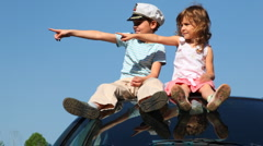 Boy and his sister sit on roof of car - stock footage
