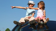 Stock Video Footage of Boy and his sister sit on roof of car