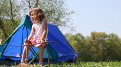 Little girl sits on chair near small tent Stock Footage