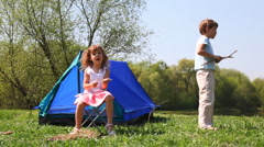Little boy and girl plays near blue tent Stock Footage