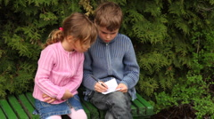 Boy and girl sit on bench near trees Stock Footage
