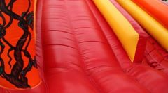 Boy drives off with inflatable rubber slides Stock Footage
