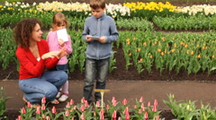 Boy writes information about flowers, near of its mother and sister Stock Footage