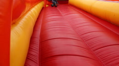 Boy drives off sitting and bouncing with inflatable rubber slides Stock Footage