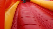 Stock Video Footage of Boy drives off sitting and bouncing with inflatable rubber slides