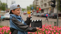 Boy claps clapperboard and goes out of frame at bed with tulips on city streets Stock Footage