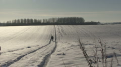 Man walks on snow covered countryside track. - stock footage