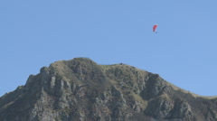Paraglider soars high above a peak Stock Footage