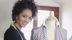 Self-employed young woman working in fashion design studio - stock footage