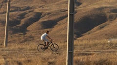Man on bicycle riding through the hills 02 Stock Footage