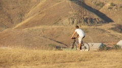Man on bicycle riding through the hills 04 Stock Footage