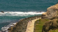 Puerto Rico - People on Sidewalk along the waterfront below El Morro Fortress Stock Footage
