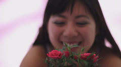 Young Chinese woman admires a mini rose giggle smile with rack focus - stock footage