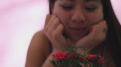 Young Chinese woman admires a mini rose comes close for a smell Stock Footage