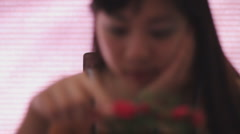 Young Chinese woman admires a mini rose in deep thought soft focus rack focus Stock Footage