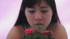 Stock Video Footage of Young Chinese woman admires a mini rose deep concern look rack focus