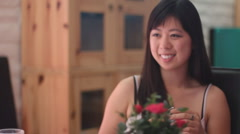 Young Chinese woman has conversation at her living room table - version 1 Stock Footage