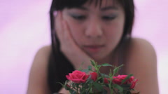 Young Chinese woman admires a mini rose and gets interrupted by young boy - stock footage