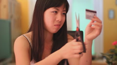 Young woman and the credit card dilemma - 5 - cut that card in half Stock Footage