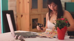 Young Chinese woman clips coupons - series 2 - flip page and cut Stock Footage