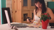 Stock Video Footage of Young Chinese woman clips coupons - series 2 - flip page and cut