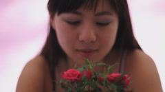 Young Chinese woman admires a mini rose humble look rack focus Stock Footage