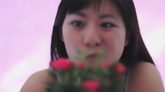 Young Chinese woman admires a mini rose big eyes smirk rack focus Stock Footage
