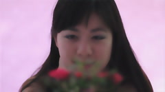 Young Chinese woman admires a mini rose soft look rack focus Stock Footage