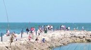 Beach scenic slow pulback of people walking on fishing jetty and people on th Stock Footage