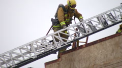 Firefighters climb down ladder - stock footage