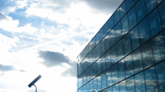 Clouds flying over a glassy modern office building. Timelapse. Stock Footage