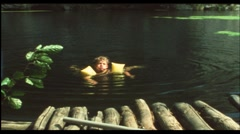 Boy swimming in lake (Vintage 8 mm amateur film) - stock footage