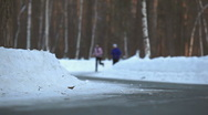 HD: a girl and a guy jogging in the forest in winter  Stock Footage