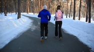 HD steadycam: a girl and a guy jogging in the forest in winter  Stock Footage