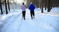 HD steadycam: a girl and a guy jogging in the forest in winter. Montage. Stock Footage
