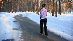 HD steadycam: a girl jogging in the forest in winter  - stock footage