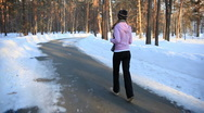 HD steadycam: a girl jogging in the forest in winter  Stock Footage