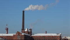 Smoke from the brick chimney, winter time, against fresh blue sky Stock Footage
