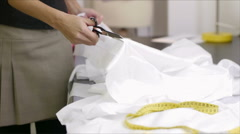Wedding dress: tailor cutting white silk fabric for bridal gown Stock Footage