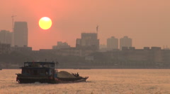 China Guangzhou sunset over Pearl river, cargo vessel sails towards the skyine Stock Footage