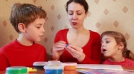 Woman works with children on table, boy sculpts figure plasticine Stock Footage