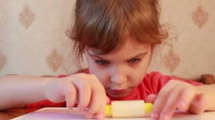 Girl rolls cylinder of plasticine on table Stock Footage