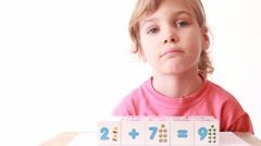 Girl play wooden blocks with numbers, builds wall of cubes Stock Footage