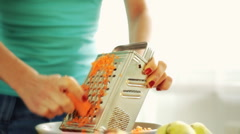 Female hands grating carrot on grater, steadicam shot Stock Footage