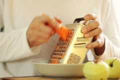Man grating carrot on grater and eating carrot, steadicam shot Stock Footage