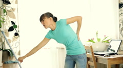 Woman having back pain during cleaning floor with mop  Stock Footage