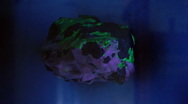Fluorescent rock under UV and white light Stock Footage