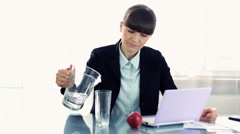 Young businesswoman drinking water at work Stock Footage