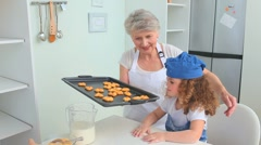 Grandmother and her grand daughter trying cookies Stock Footage