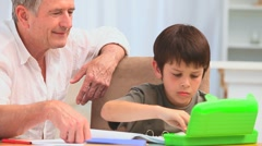 Cute little boy colouring with his grandfather Stock Footage